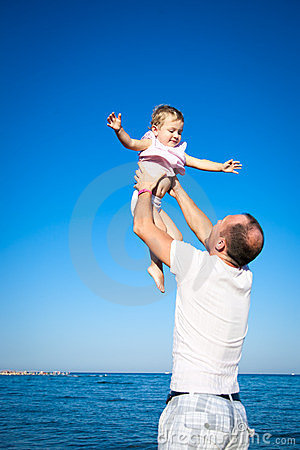 Happy child playing with father at the beach