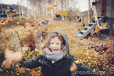 Happy child playing with leaves in autumn. Seasonal outdoor activities with kids Stock Photo