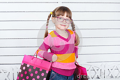 Happy child with shopping bags. She is enjoying the gifts and holidays