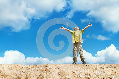 Happy child standing with hands raised up over sky