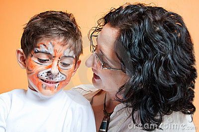 Happy child in tiger make-up and mother