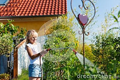 Happy child watering flowers
