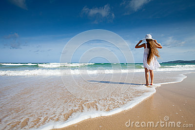 Happy child in white dress on sea beach