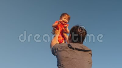 Happy childhood concept. father throws up his child in blue sky Dad plays with a little daughter, the baby smiles and. Happy childhood concept. father throws up stock video