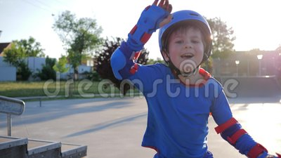 Happy childhood, joyful kid in helmet actively spends leisure at Skate Park on open air in sunlight. Happy childhood, joyful kid in helmet actively spends stock video footage