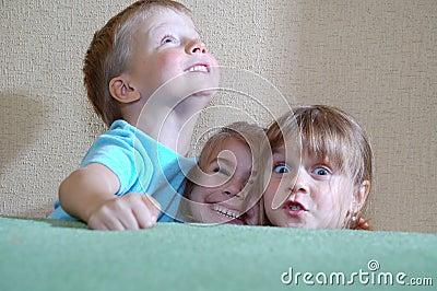 Happy children hiding behind the sofa