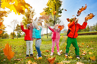 Happy children playing with flying leaves in park