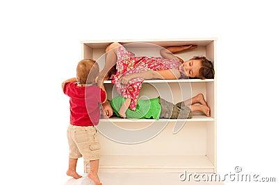 Happy children playing on fun kids bookshelf