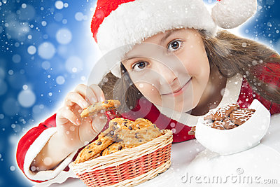 Happy Christmas girl eating Christmas cookies