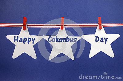 Happy Columbus Day message greeting written across white star cards hanging from red stripes ribbon and pegs on a line