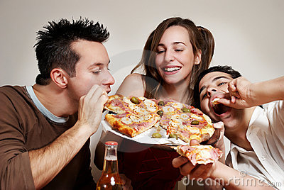 Happy company of youth eating a pizza