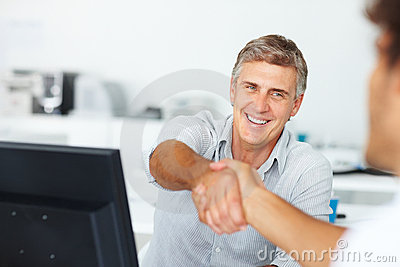 Happy consultant shaking hands with a colleague