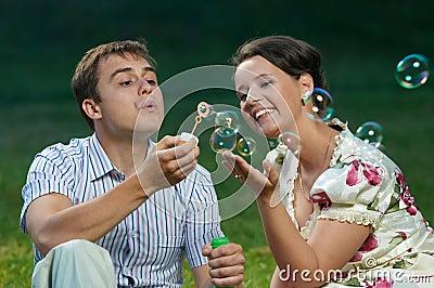 Happy couple blowing soap bubbles