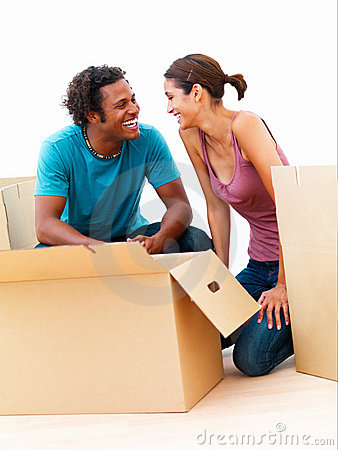 Happy couple with boxes in their new house
