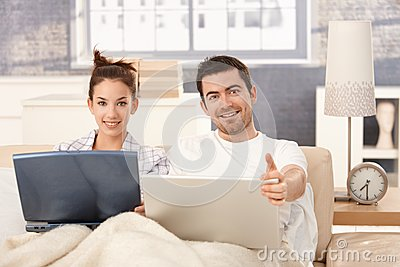 Happy couple browsing internet in bed at home