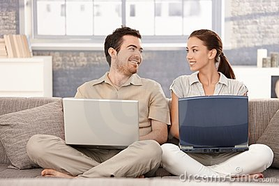 Happy couple browsing internet having fun smiling