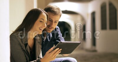 Couple browsing tablet content in the night. Happy couple browsing tablet content in the night in the street stock footage