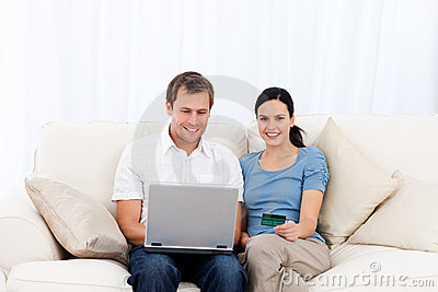 Happy couple buying online with laptop and cd