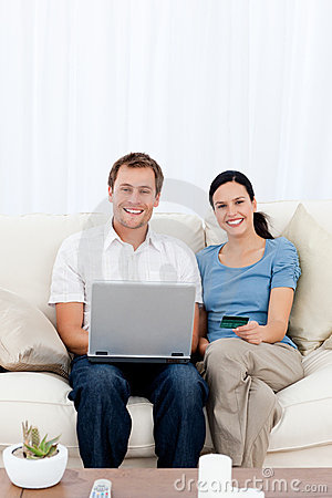 Happy couple buying online with their credit card