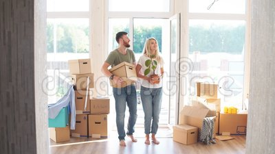 Happy Couple Carrying Cardboard Boxes Into New Home On Moving Day. Happy young Couple Carrying Cardboard Boxes Into New Home On Moving Day stock footage