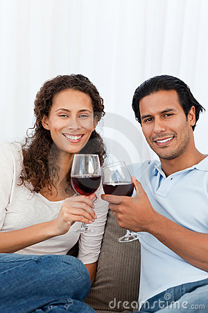 Happy couple clinking glasses of red wine