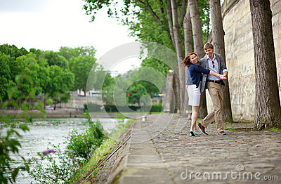 Happy couple is dancing on the Seine embankment