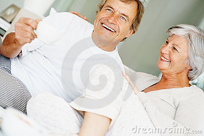 Happy couple drinking coffee while in bed