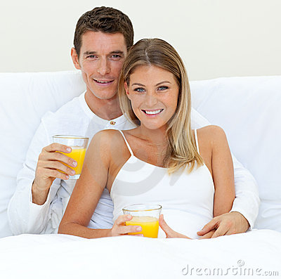 Happy couple drinking orange juice on their bed