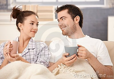 Happy couple drinking tea in bed smiling