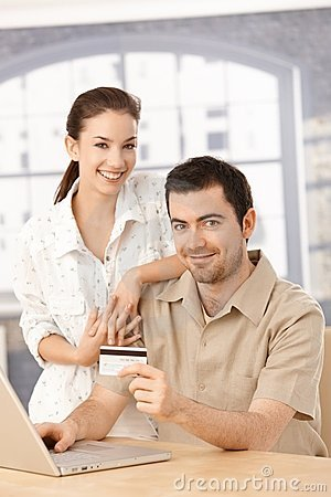 Happy couple enjoying online shopping smiling