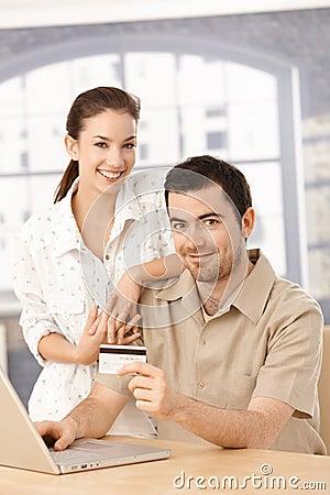 Happy couple enjoying online shopping smiling
