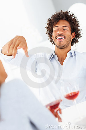 Happy couple enjoying over a glass of red wine