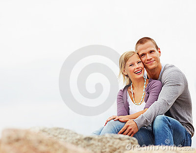 Happy couple enjoying on the rocks by the beach