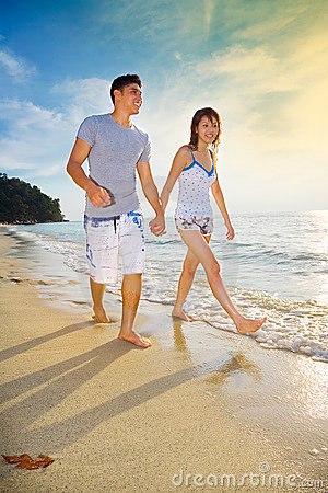 Happy couple enjoying walking along sunset beach
