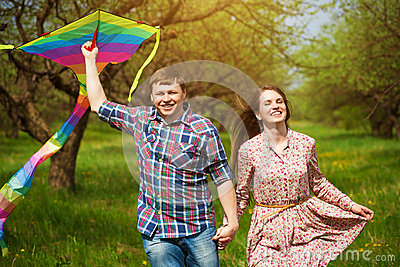 Happy couple are fling a kite on a spring meadow