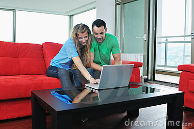 Happy couple have fun and work on laptop at home