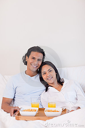 Happy couple having breakfast in the bed