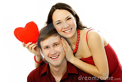 Happy couple with a heart-shaped pillow