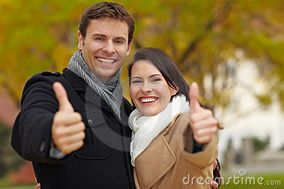Happy couple holding thumbs up
