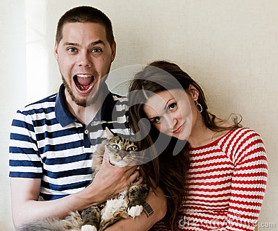 Happy couple at home with their cat