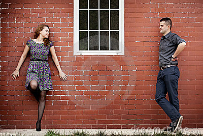Happy couple and house with brick wall