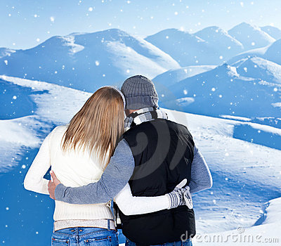 Happy couple hugging outdoor at winter mountains
