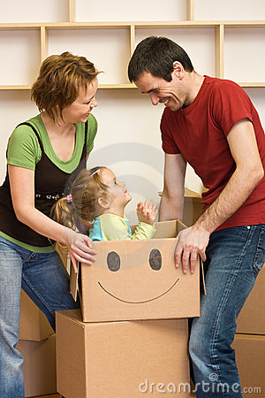 Happy couple with a kid unpacking in a new home