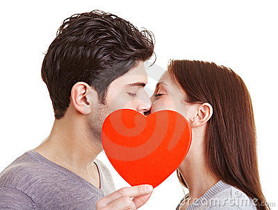 Happy couple kissing behind heart