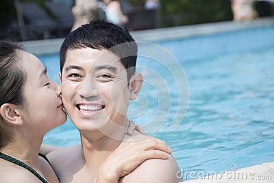 Happy couple kissing and looking at camera in the pool