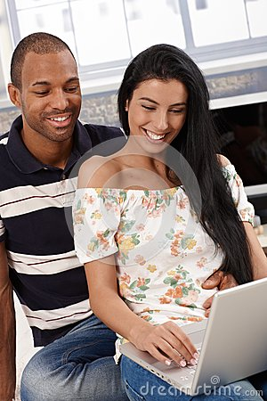 Happy couple with laptop computer at home