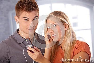Happy couple listening to music via earphones