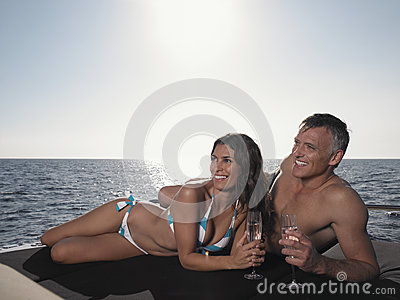 Happy Couple Looking Away While Lying On Yacht