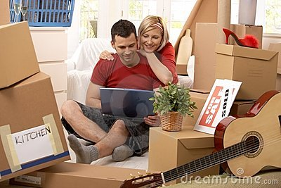 Happy couple looking at computer in new house