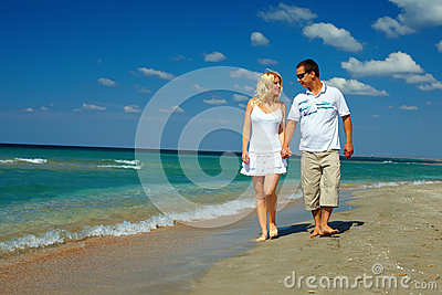 Happy couple in love walking on sea shore